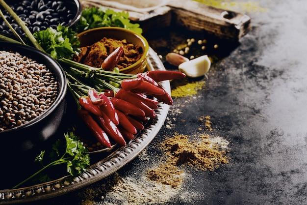 Schöne leckere appetitanregende zutaten gewürze lebensmittel für das kochen gesunde küche. dunkler schwarzer hintergrund horizontaler toning textfreiraum