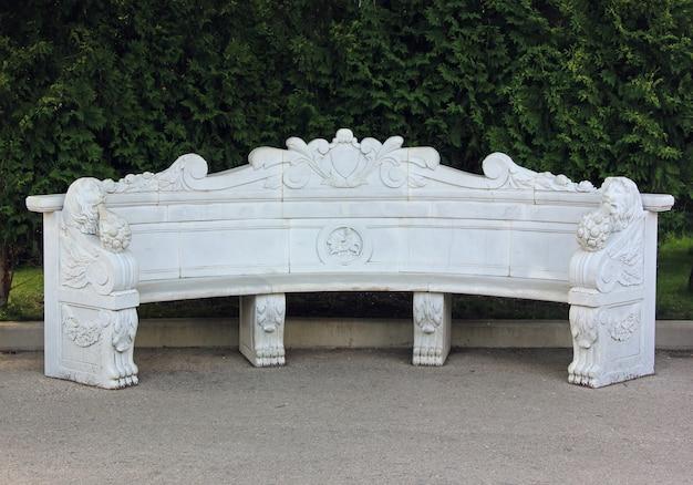 Schöne leere bank des weißen steins mit carvings im park.