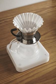 Schöne leere filterkaffeemaschine mit glänzender chromschale oben und sauberem papierfilter ist bereit, gefilterten kaffee zuzubereiten. isoliert auf weißen gewichten auf holztisch im cafégeschäft
