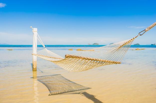 Schöne leere hängematte um tropischen strandseeozean für feiertagsferien