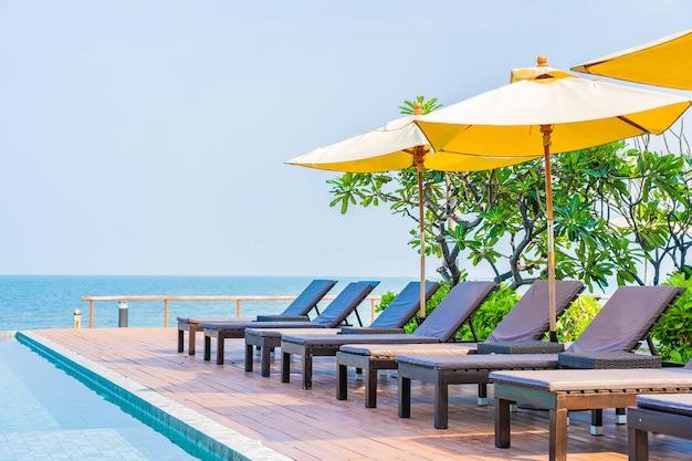 Schöne leere stühle und regenschirme um swimmingpool im freien im hotelerholungsort