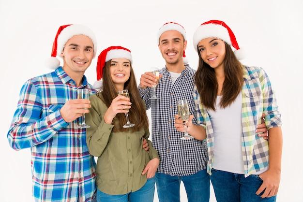 Schöne leute in weihnachtsmützen, die weihnachten mit champagner feiern