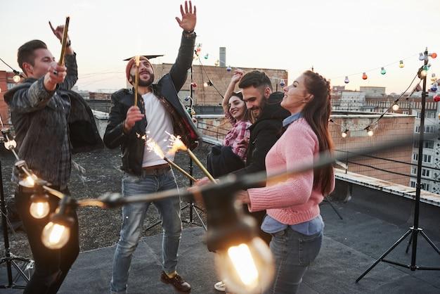 Schöne leute. spielen mit wunderkerzen auf dem dach. gruppe junger schöner freunde