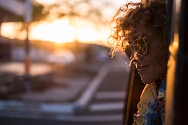Schöne licht und junge frau mit lockigem haar rportrait mit sonnenuntergangslicht auf gesicht und sonnenbrille