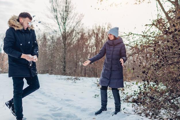 Schöne liebevolle paare, die zusammen schneebälle im winterwald spielen. leute, die spaß draußen haben