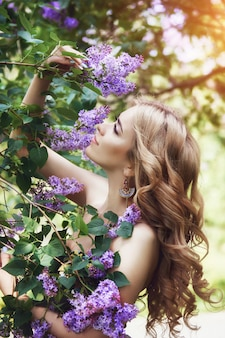 Schöne lila blume der jungen frau der mode im freien
