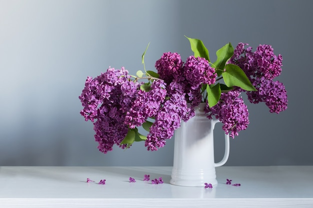 Schöne lila blumen im weißen krug auf weißem holztisch