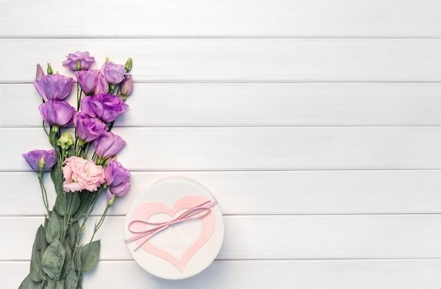 Schöne lila eustoma blumen und handgemachte geschenkbox auf weißem holzhintergrund. speicherplatz kopieren, draufsicht,