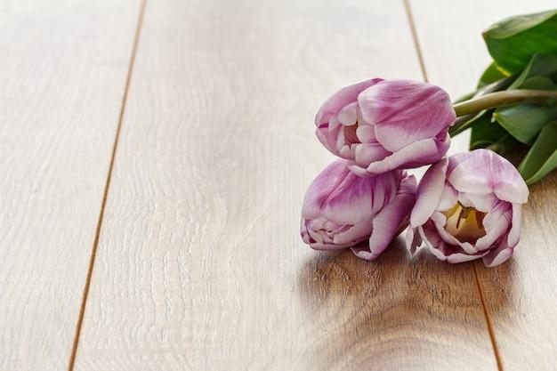 Schöne lila tulpen auf den holzbrettern. konzept, an feiertagen ein geschenk zu machen.