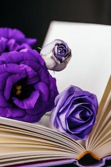 Schöne lila violette eustoma oder lisianthus oder prärie enzian blumen und buch auf dunklem hintergrund. speicherplatz kopieren