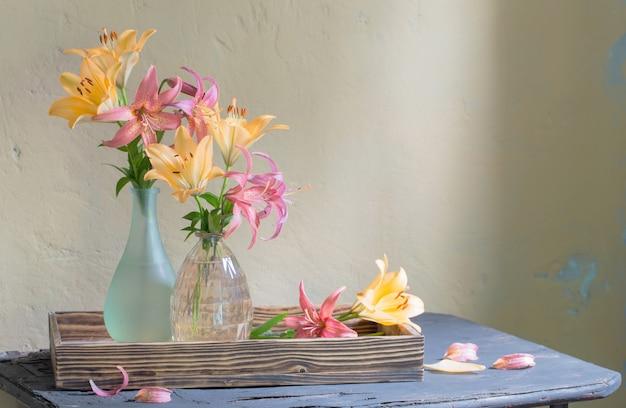 Schöne lilie in glasvase auf altem holzregal