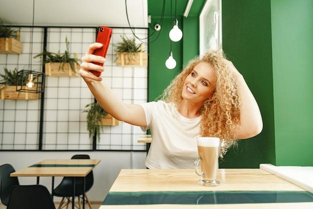 Schöne lockige blonde frau, die selfie beim sitzen am tisch im kaffeehaus nimmt