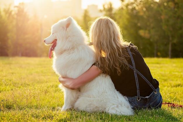Schöne lockige blonde glückliche junge frau in denim-shorts, die am glas sitzt und einen weißen, flauschigen, süßen samojeden-hund im sommerpark-sonnenuntergang-strahlen-feld-hintergrund umarmt. rückansicht von haustier und gastgeberin