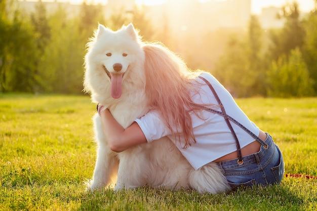 Schöne lockige blonde glückliche junge frau in denim-shorts, die einen weißen flauschigen süßen samojedenhund im sommerpark-sonnenuntergangstrahlen-feldhintergrund umarmt. rückansicht von haustier und gastgeberin.