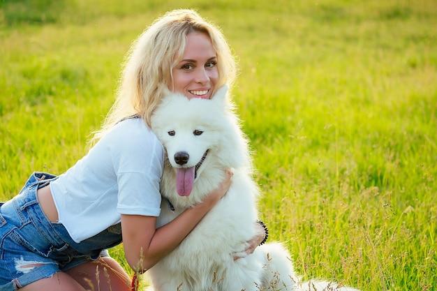 Schöne lockige blonde lächelnde glückliche junge frau in denim-shorts, die spielt, umarmt einen weißen, flauschigen, süßen samojeden-hund im sommerpark-sonnenuntergang-strahlen-feldhintergrund. haustier und gastgeberin