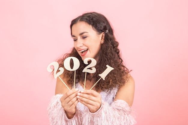 Schöne lockige brünette frau mit nackten schultern hält holznummer für das neujahrskonzept