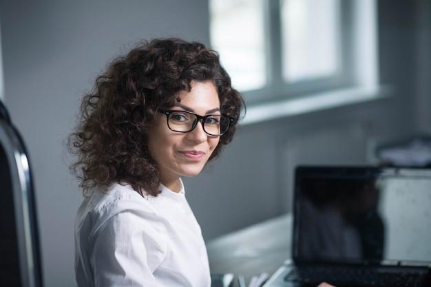 Schöne lockige brünette geschäftsfrau mit brille am arbeitsplatz im büro