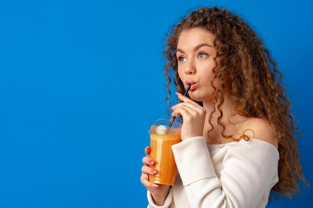 Schöne lockige frau, die orangensaft vor blauem hintergrund trinkt