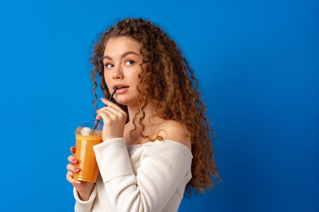 Schöne lockige frau, die orangensaft vor blauem hintergrund trinkt Premium Fotos
