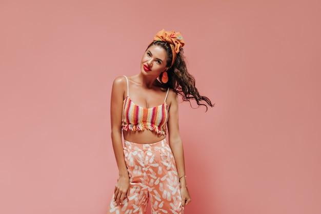 Schöne lockige frau mit stilvollen accessoires in modischer, heller kleidung, die ihr haar spielt und nach vorne schaut