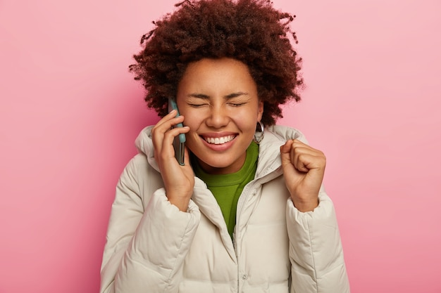 Schöne lockige frau ruft freund über modernes smartphone an, hebt geballte faust, lächelt breit, trägt weiße jacke mit kapuze, modelle vor rosa hintergrund.