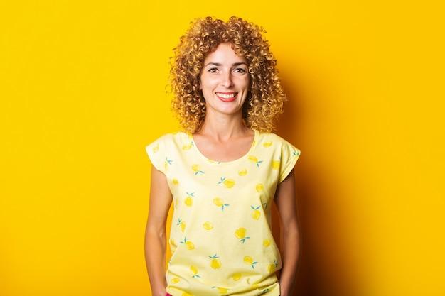 Schöne lockige junge frau auf einem hellen gelben hintergrund