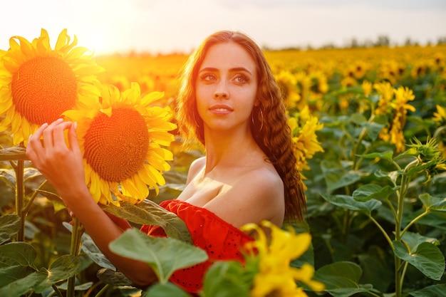 Schöne lockige junge frau im sonnenblumenfeld, die sonnenblumenblume in der hand hält porträt des jungen w...