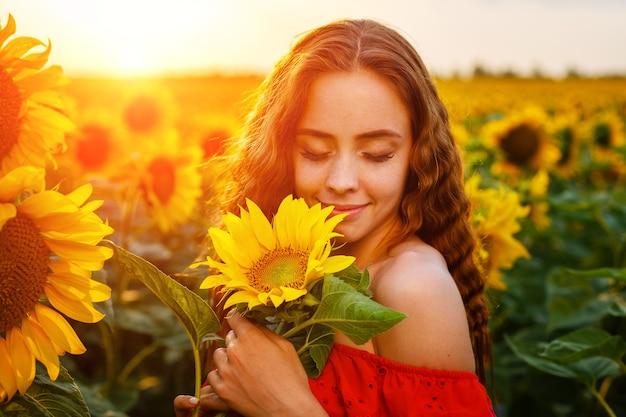Schöne lockige junge frau im sonnenblumenfeld, die sonnenblumenblume in der hand hält