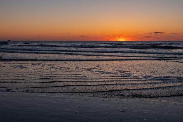 Schöne lodernde sonnenunterganglandschaft in schwarzem meer und in orange himmel über ihm mit goldener reflexion der fantastischen sonne auf ruhigen wellen als. erstaunliche sommersonnenuntergangansicht über den strand. russische natur, sotschi
