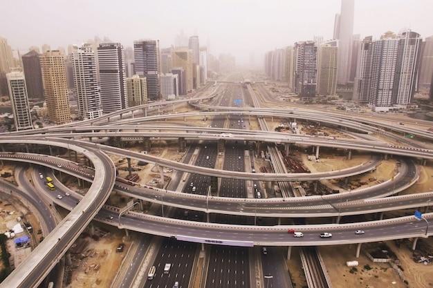 Schöne luftaufnahme der futuristischen stadtlandschaft mit straßen, autos, zügen, wolkenkratzern. dubai