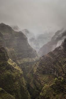 Schöne luftaufnahme von felsigen und nebligen bergen des waimea canyon, usa