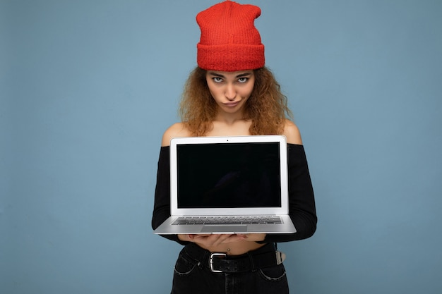Schöne lustige amüsante nachdenkliche junge dunkelblonde lockige frau, die schwarzes bauchfreies top und rot trägt und