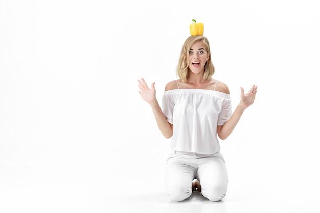 Schöne lustige blonde frau in einer weißen bluse, die gelben paprika hält. gesunde ernährung und ernährung