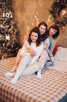 Schöne lustige frauen, die gemütliche pyjamas tragen, die auf bett kuscheln sitzen