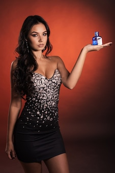 Schöne luxuriöse junge frau in einem kleid mit strasssteinen, die mit parfüm aufwerfen