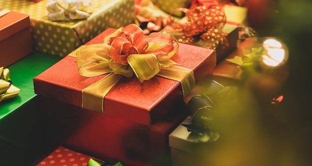 Schöne luxus-geschenkbox, umwickelt mit buntem verpackungspapier, band, verziert mit kreativer, charmanter schleife, gestapelt als gruppe von besonderen wunderschönen geschenken und souvenirs für die weihnachtsfeier