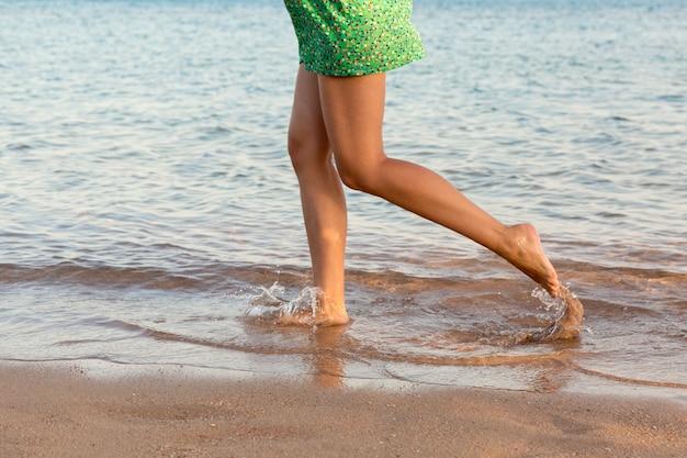 Schöne mädchen beine am strand laufen. hübsches mädchen, das auf wasser geht
