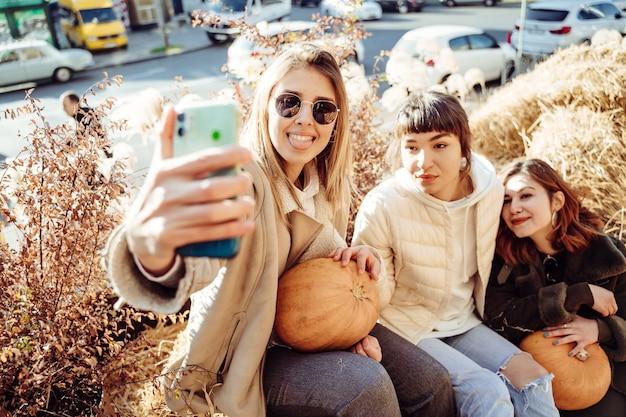 Schöne mädchen, die auf heuhaufen sitzen, machen ein selfie
