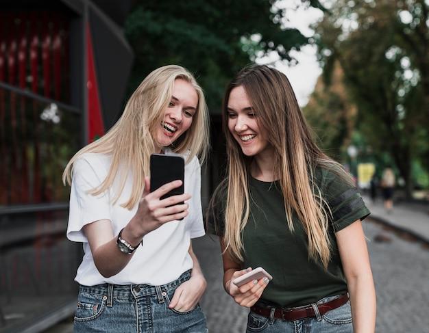 Schöne mädchen, die ein selfie mit telefon nehmen