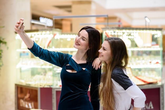 Schöne mädchen, die im einkaufszentrum selfi tun.