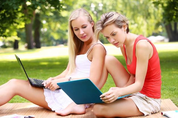 Schöne mädchen, die laptops an einem park verwenden