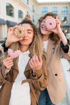 Schöne mädchen, die mit köstlichen donuts aufwerfen