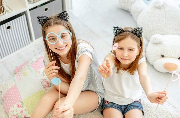 Schöne mädchen, die spaß mit brille und lippen auf stöcken im spielzimmer haben