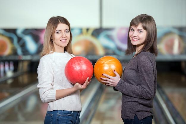 Schöne mädchen im bowling club halten bälle.