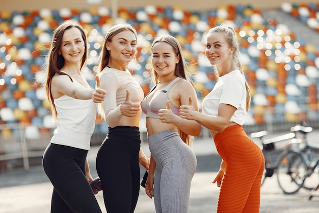 Schöne mädchen im stadion. sportmädchen in einer sportbekleidung. die leute schauen in die kamera.