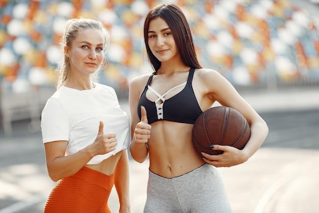 Schöne mädchen im stadion. sportmädchen in einer sportbekleidung. leute mit baskettballball.