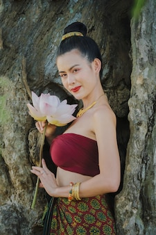 Schöne mädchen im traditionellen kostüm schöne junge frau im trachtenkleidkostüm mit den händen, die rosa des lotos halten.