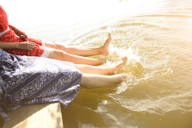Schöne mädchen in der nähe von fluss in vintage-kleidern. barfüßige frauen waschen die füße im wasser. freunde, die urlaub genießen. rustikale sommerwohnung. holzbrücke. sonniger tag entspannen.