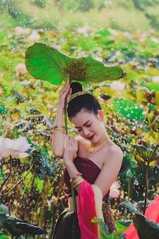 Schöne mädchen in tracht. schöne junge frau im trachtenkostüm mit den händen, die blatt von lotos halten.