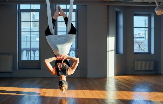 Schöne mädchen luft yoga trainer zeigt medutiruet auf hängenden linien kopfüber in einem yoga-raum